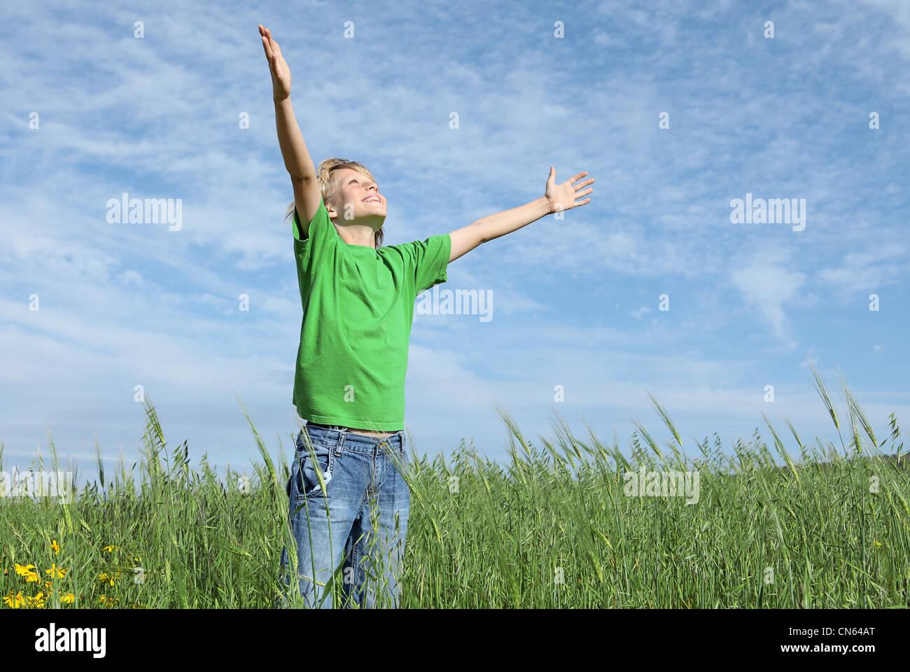 Bambino felice a braccia alzate lodando il cielo in estate Immagini Stock