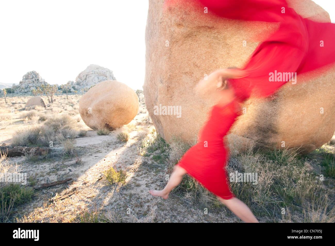 Sfocata donna rosso gettando la sua sciarpa rossa in un paesaggio di pietra. Immagini Stock