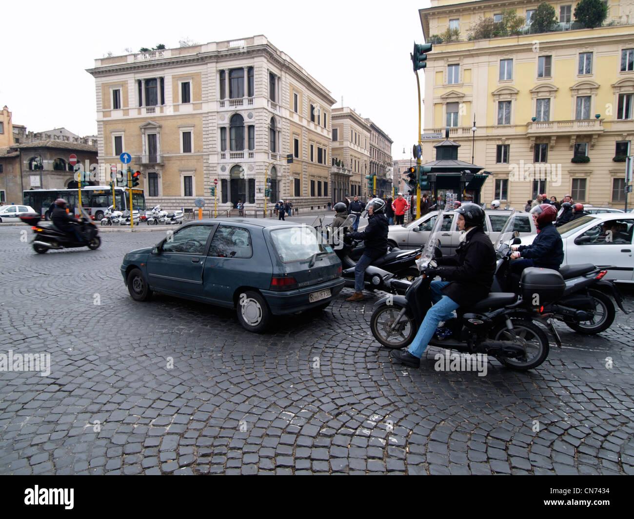 Molte automobili e scooter in attesa di un semaforo a Roma Italia caotica trafficata Piazza Ponte Umberto I Immagini Stock