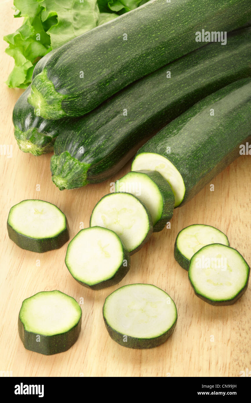 Zucchine o la zucchina tagliata a fette sul bordo di taglio Immagini Stock