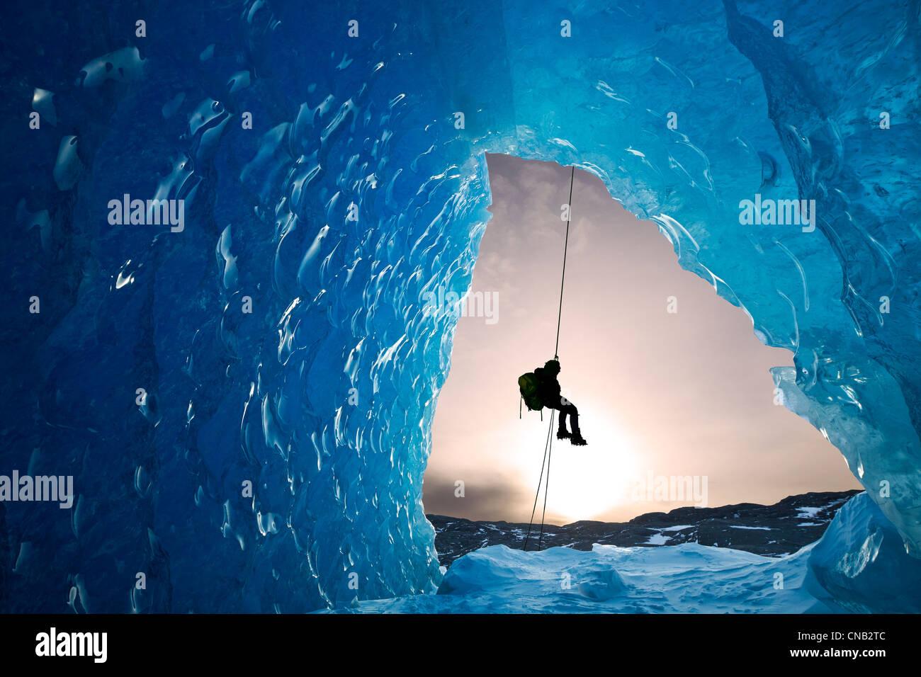 Composito: vista dall'interno di una caverna di ghiaccio di un iceberg come un alpinista rappels giù, Mendenhall Immagini Stock