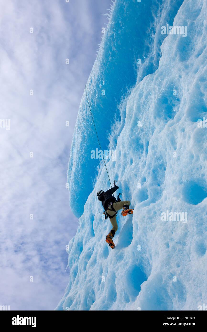 Un alpinista ascende al volto di un grande iceberg congelati in Mendenhall Lago, Juneau, a sud-est di Alaska, inverno Immagini Stock