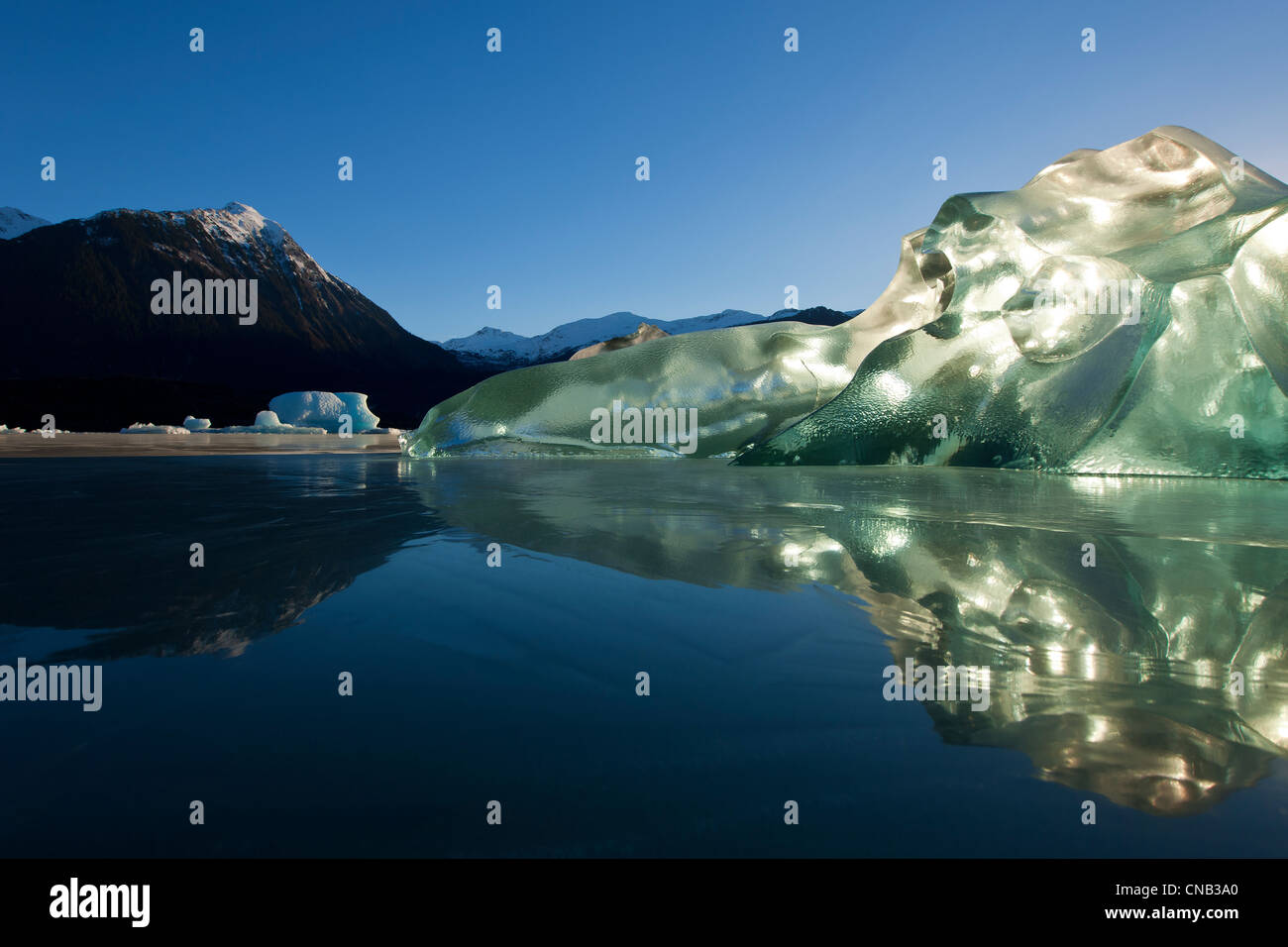 Un iceberg, intrappolati nelle acque congelate di Mendenhall Lago incandescente e retroilluminato con il sole del Immagini Stock