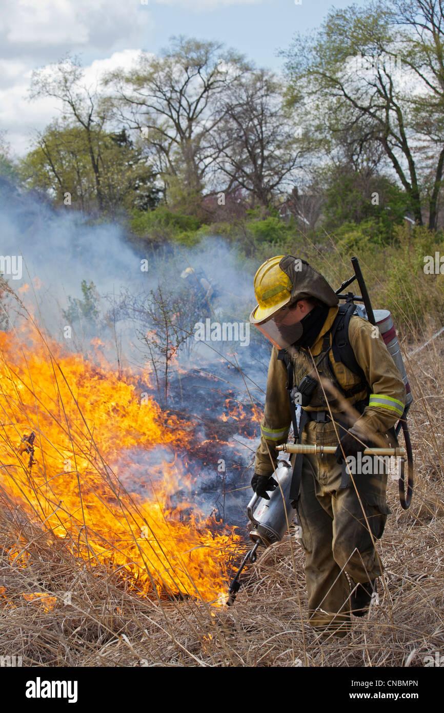 I lavoratori di indossare abbigliamento protettivo bruciare parti di River Rouge Park a Detroit con lo scopo di Foto Stock