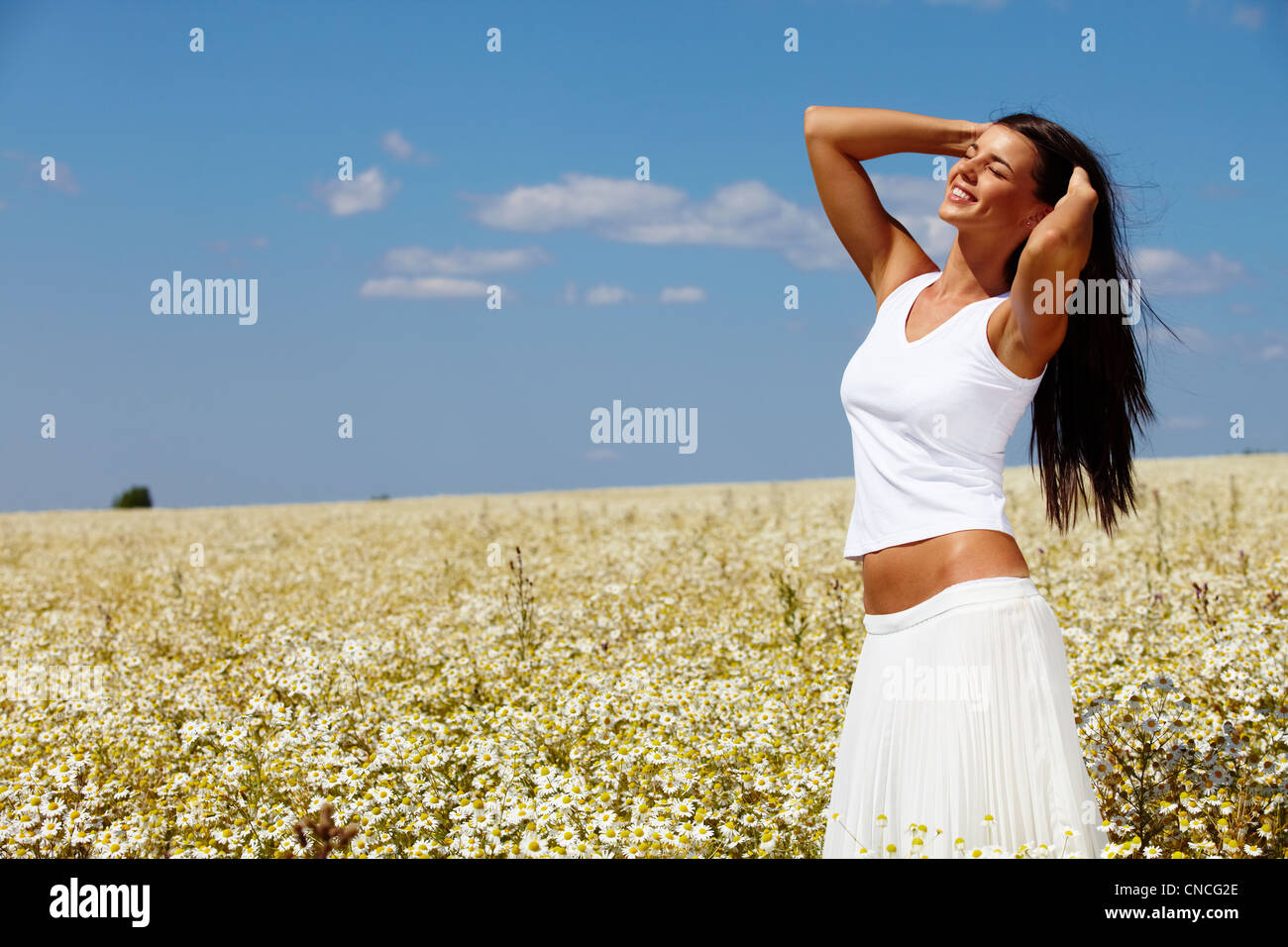 Giovane donna vestita di bianco in piedi tra chamomiles in una giornata di sole Foto Stock