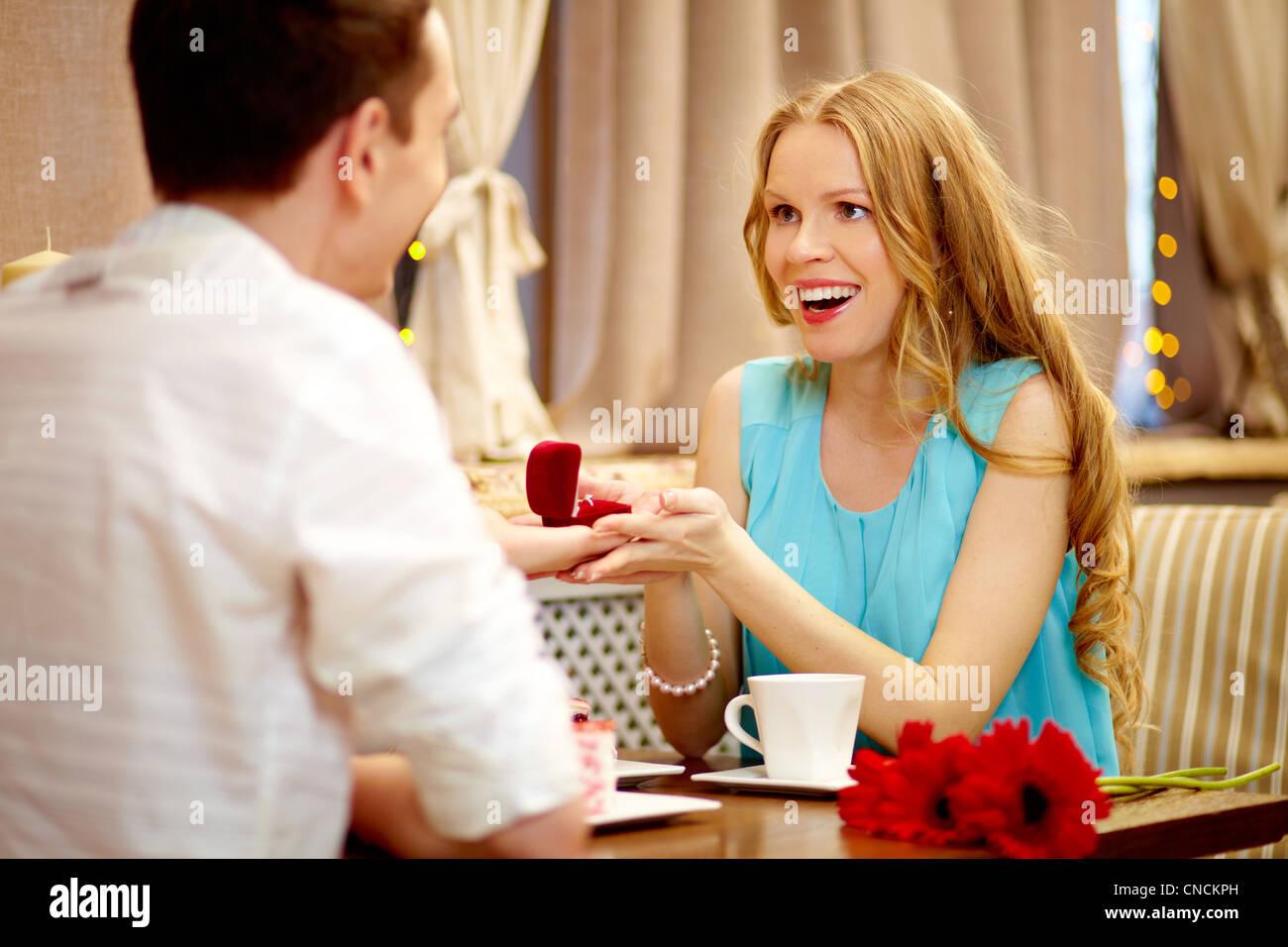 Stupito donna che guarda il suo ragazzo che mostra dono a pranzo Immagini Stock