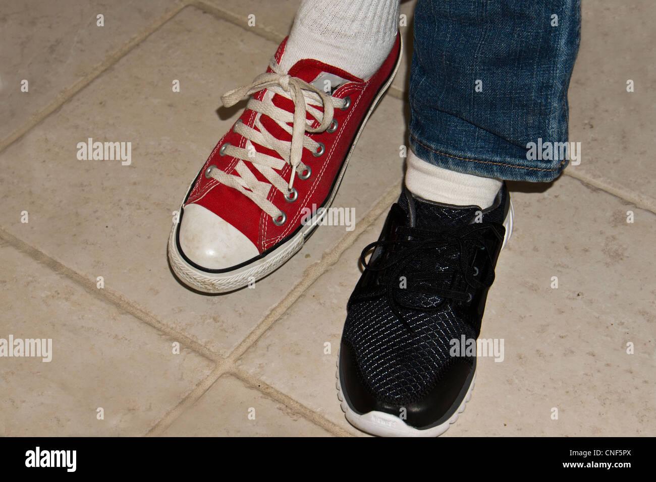 the latest 00026 d879c Donna che indossa non corrispondenti rosso nero sneakers Immagini Stock
