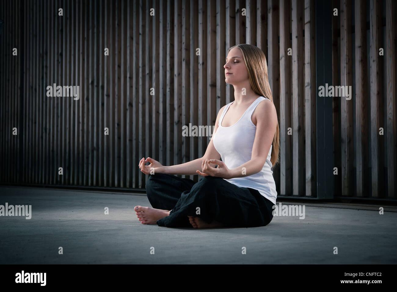 Giovane donna 20-25 seduto e ambiente di meditazione Yoga meditazione in un moderno, fresco ambiente esterno Immagini Stock