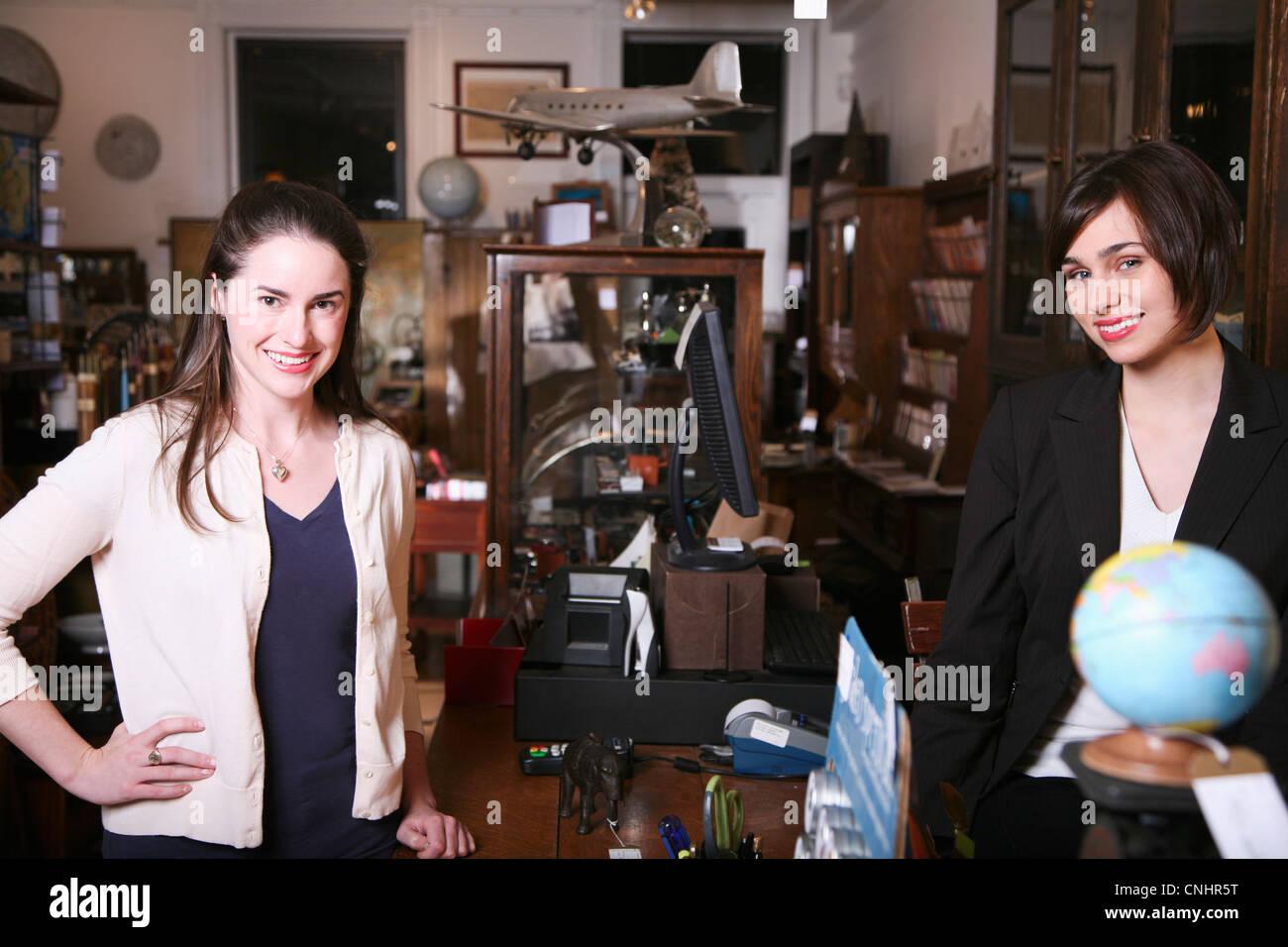 Due donne in piedi su lati opposti di un contatore in un negozio di antiquariato Immagini Stock