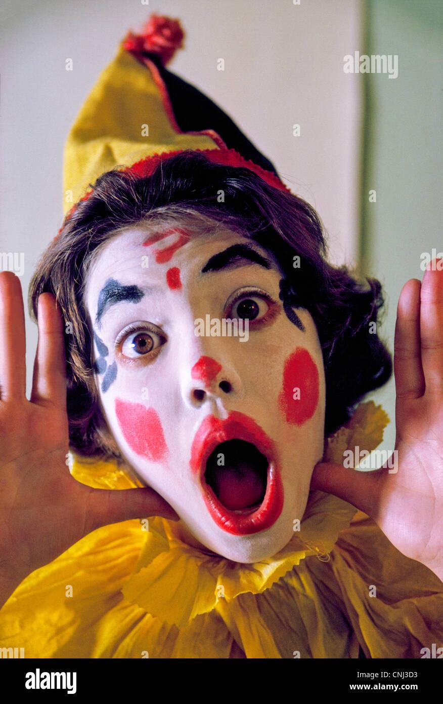 Una giovane ragazza abiti fino come un colorato circus clown per andare ingann-o-trattare durante l'annuale Immagini Stock