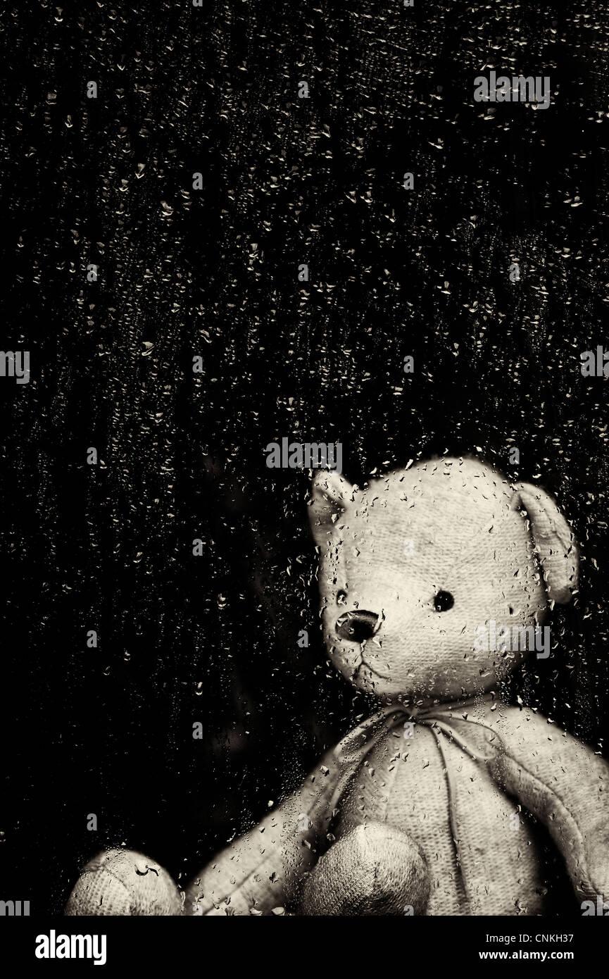 Triste orsacchiotto guardando attraverso un vetro ricoperto di gocce di pioggia. Tonalità seppia Immagini Stock