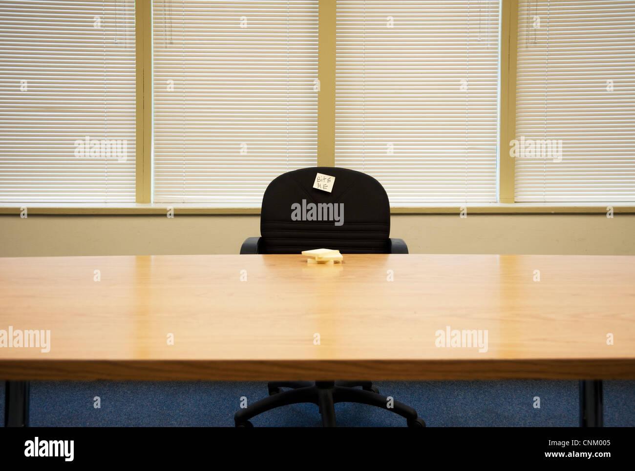 Sedia vuota al tavolo per riunioni con nota adesiva che dice 'bite me' Immagini Stock