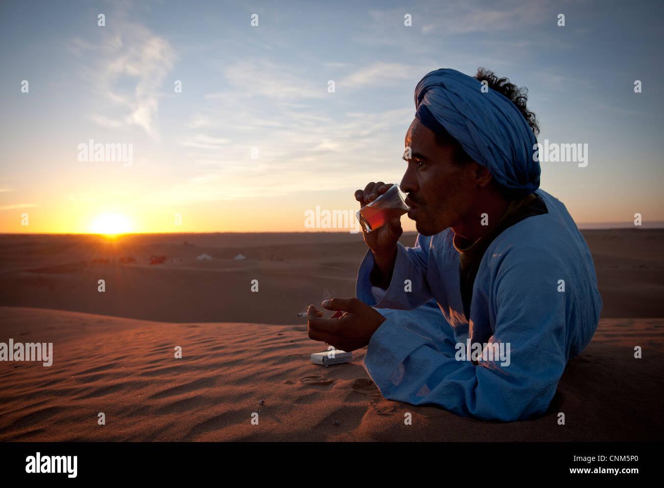 Il Nomad Berber bere il tè al tramonto nel deserto del Sahara, Erg Chigaga, Marocco Immagini Stock