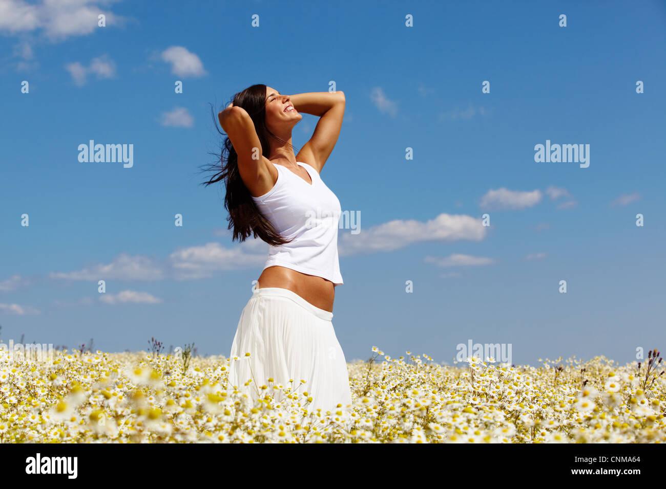 Giovane donna in bianco in piedi tra chamomiles in una giornata di sole Foto Stock