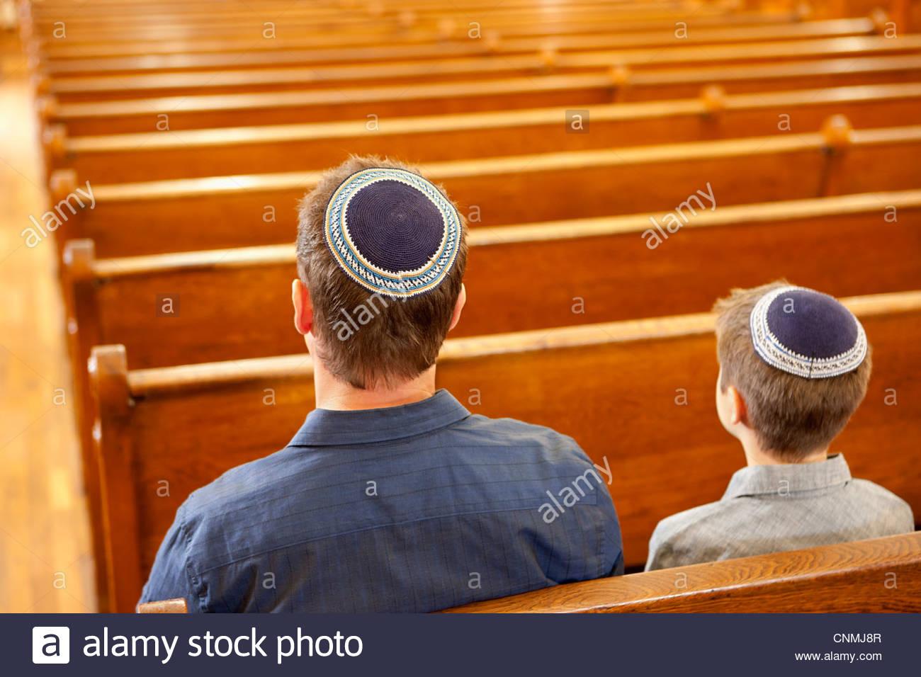 Padre e figlio in yarmulkes seduta nella sinagoga Immagini Stock
