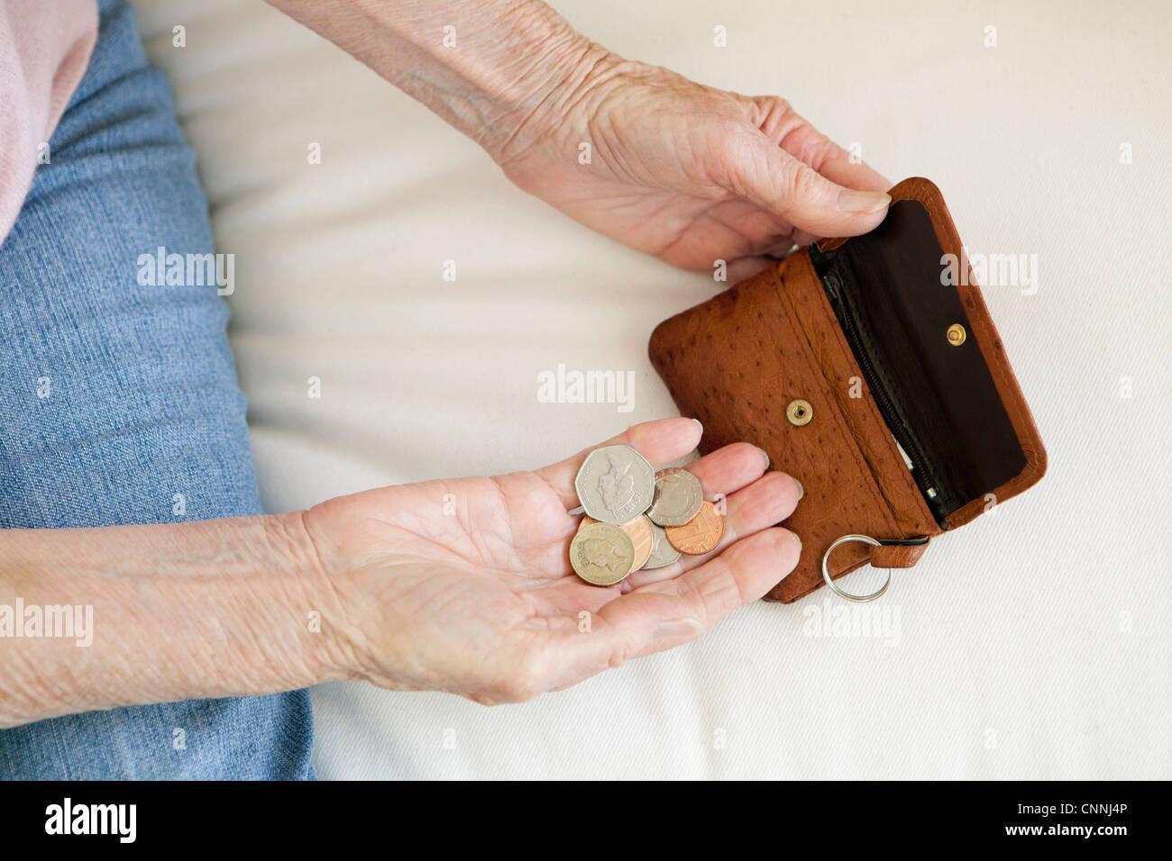 Close up della donna più anziana contare monete Immagini Stock