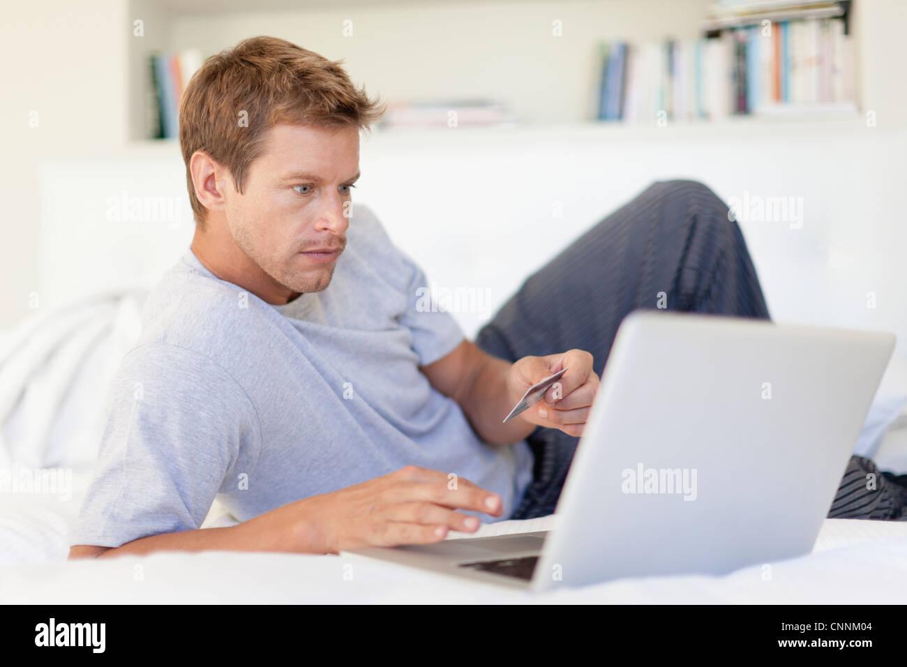 L uomo lo shopping online con il computer portatile Immagini Stock