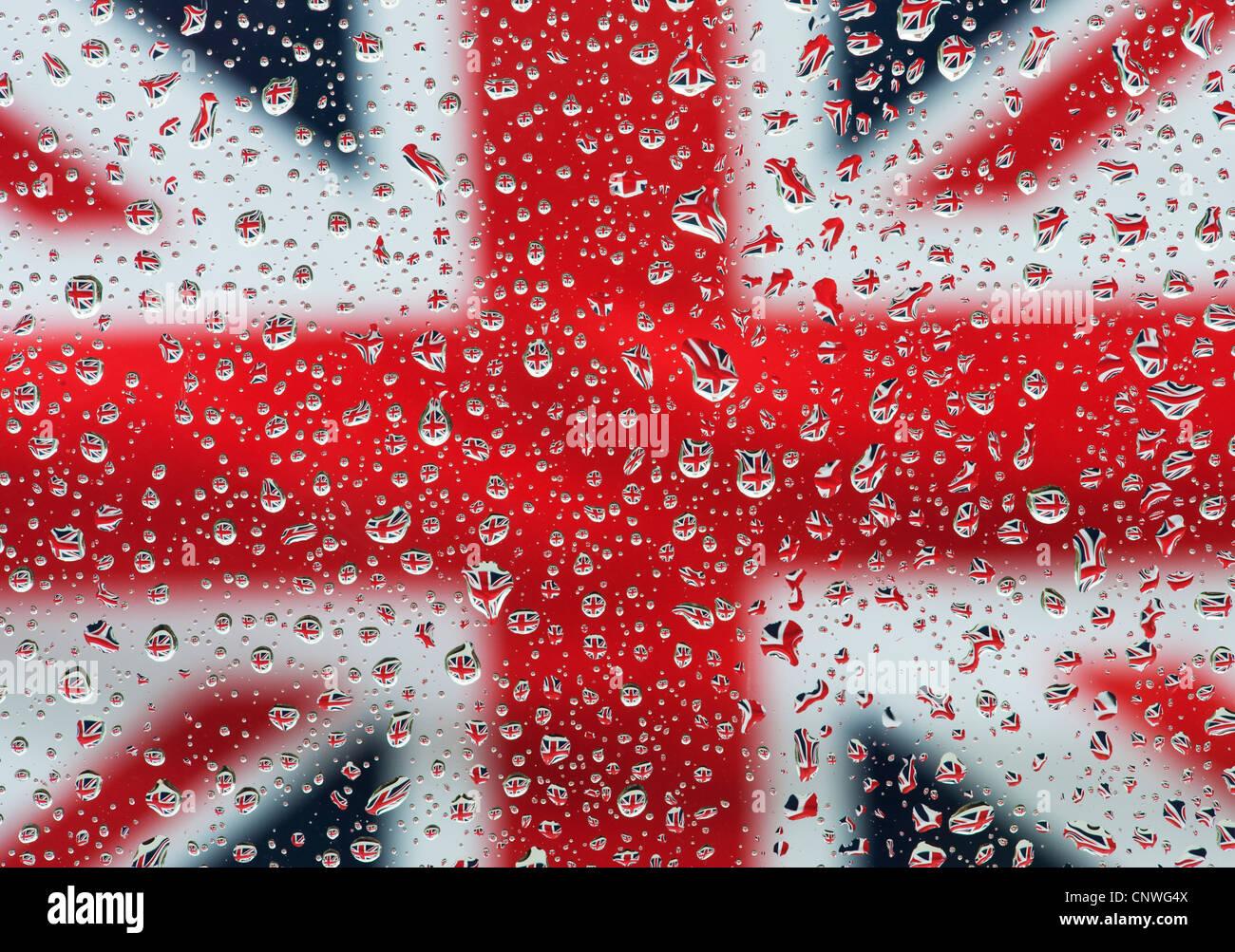 Le gocce di pioggia sul vetro di fronte a un'Unione jack flag Immagini Stock