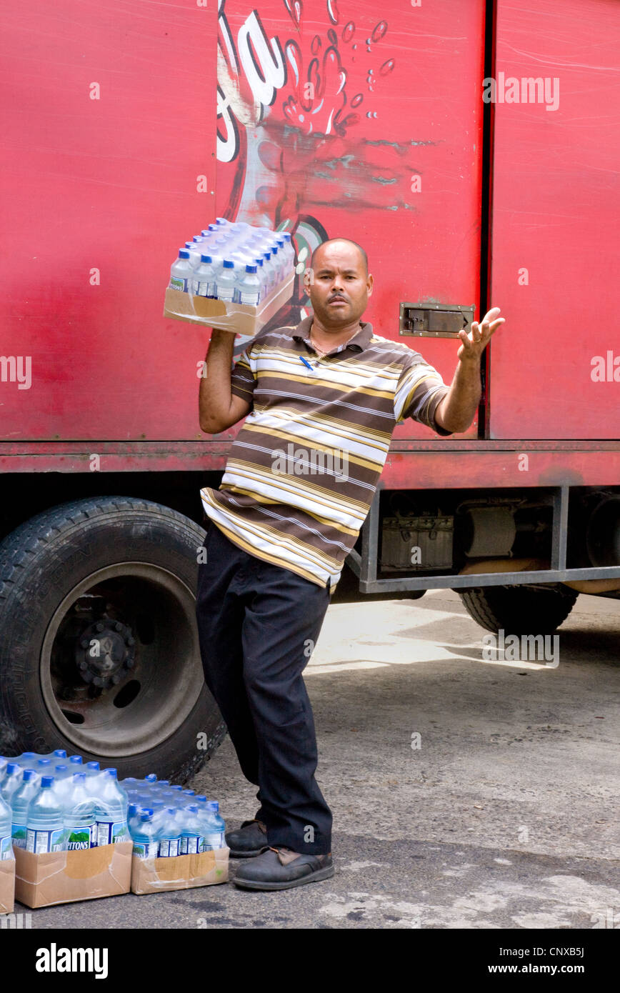 Un amichevole conducente erogare acqua in bottiglia per un villaggio supermercato in posa per una foto in Calibishie Immagini Stock