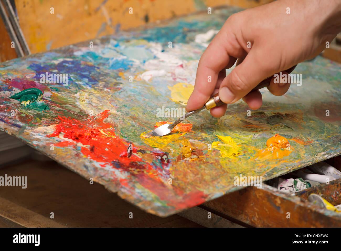Artista mix di vernici a olio con una spatola.Immagini orizzontali, close-up. Immagini Stock