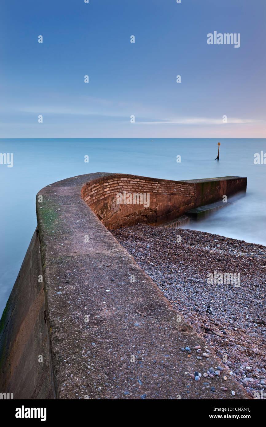 Stone jetty di Sidmouth sulla spiaggia al tramonto, Sidmouth, Devon, Inghilterra. Inverno (gennaio 2012). Immagini Stock