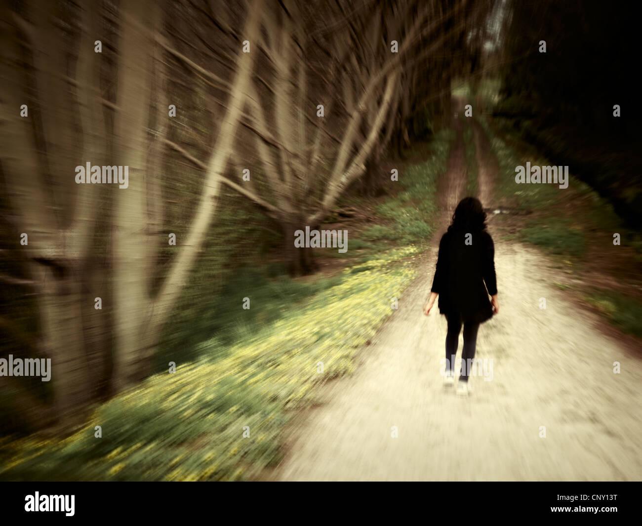 Donna cammina lungo via del bosco. Foto Stock