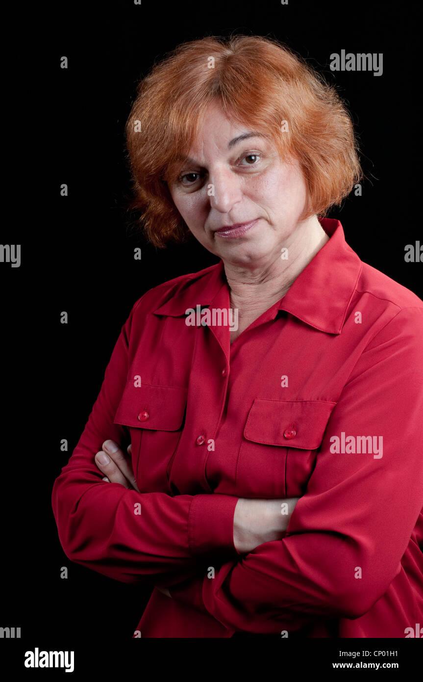 Donna di mezza età con bracci incrociati cercando gravi Immagini Stock