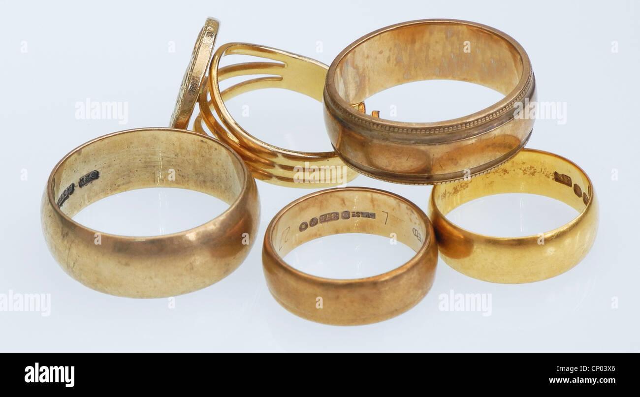 Cinque anelli in oro. I rottami in oro è elevati in ogni momento. Immagini Stock