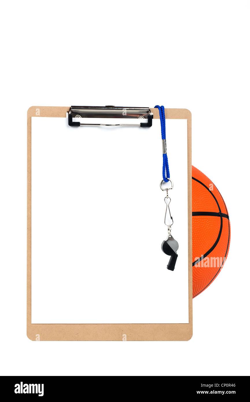 Un pullman di appunti con foglio di carta bianco, whistle e matita si appoggia contro una palla da basket ed è Immagini Stock