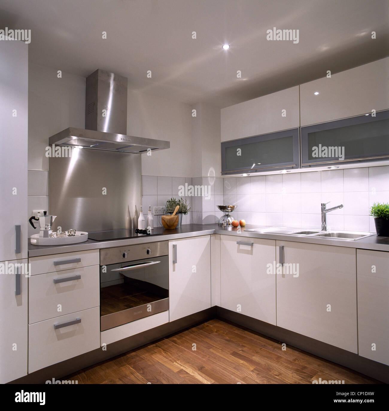Una moderna cucina bianca con le unità bianche, acciaio inox forno ...