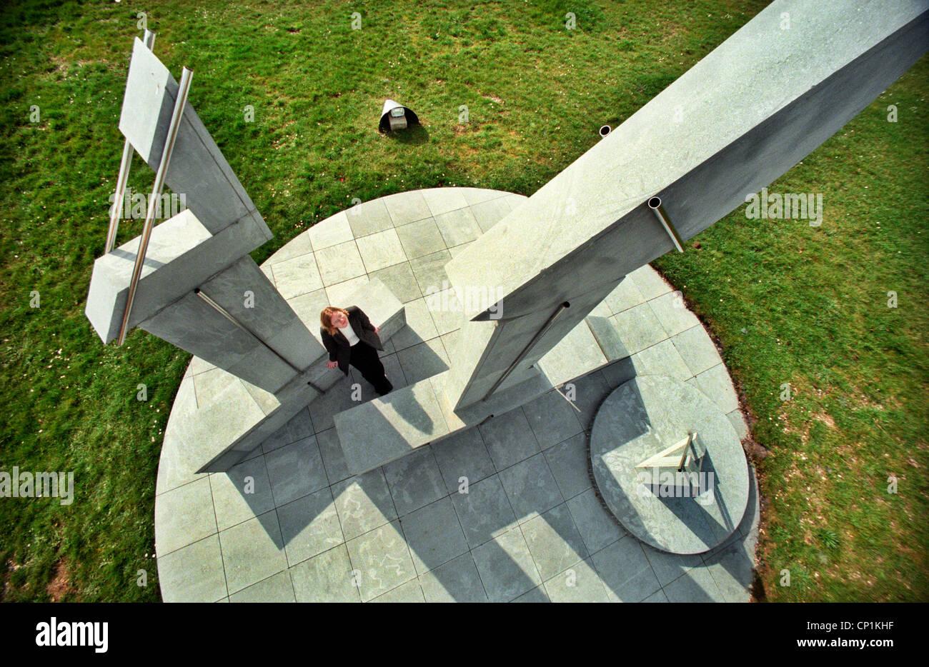 Una donna in piedi alla base di un grande e moderno di scultura astratta. Immagini Stock