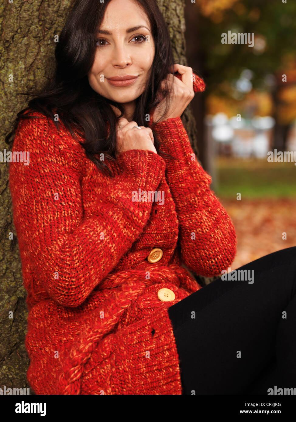 Bella sorridente giovane donna cuddling fino in un maglione rosso all'aperto in autunno Immagini Stock