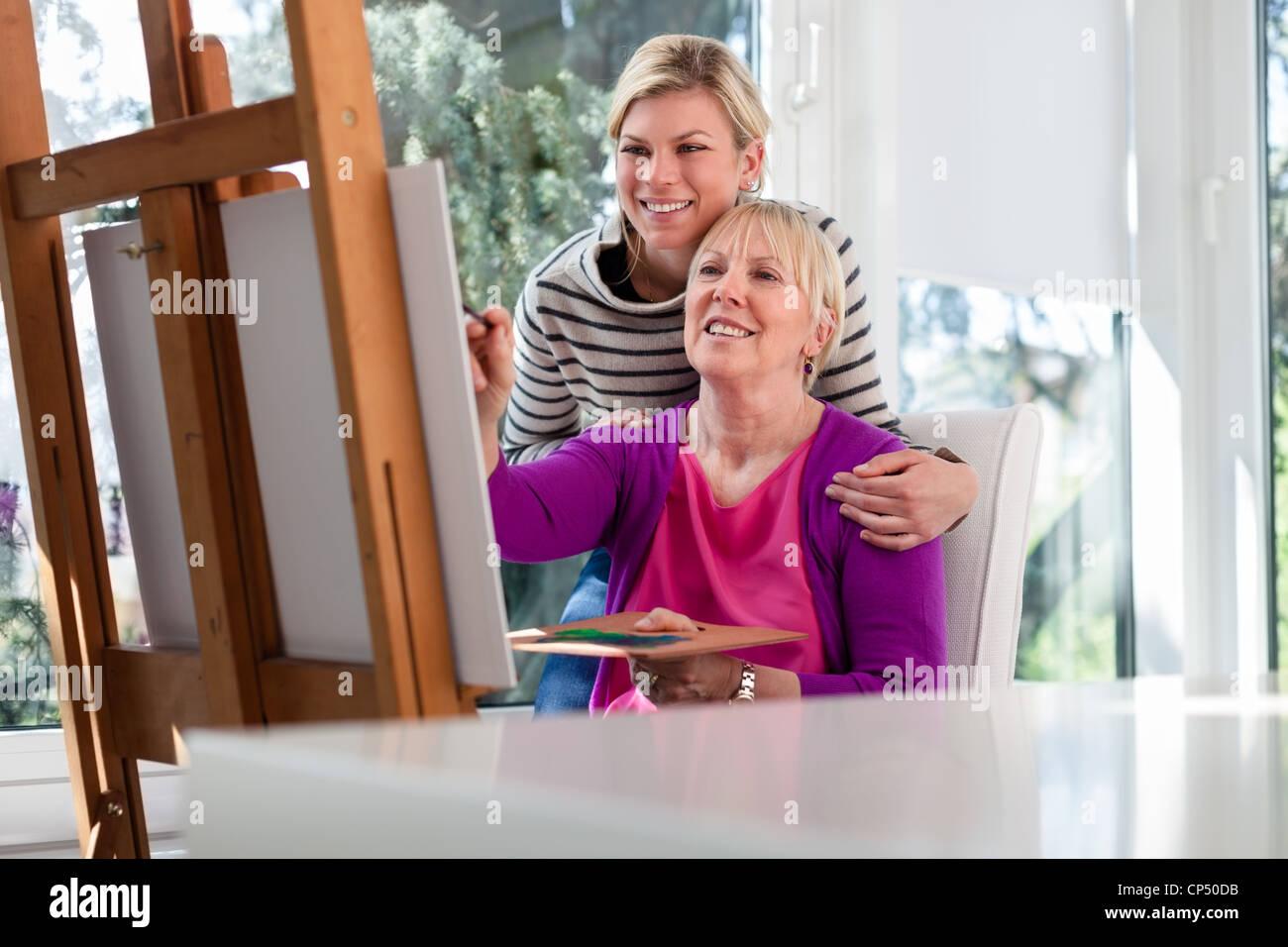 Ritratto di famiglia con felice madre pittura per hobby e la figlia sorridente e abbracciando il suo a casa Immagini Stock