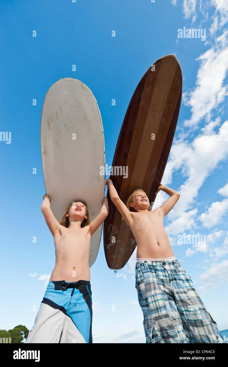 Spagna, Mallorca, bambini con tavola da surf in spiaggia Foto Stock