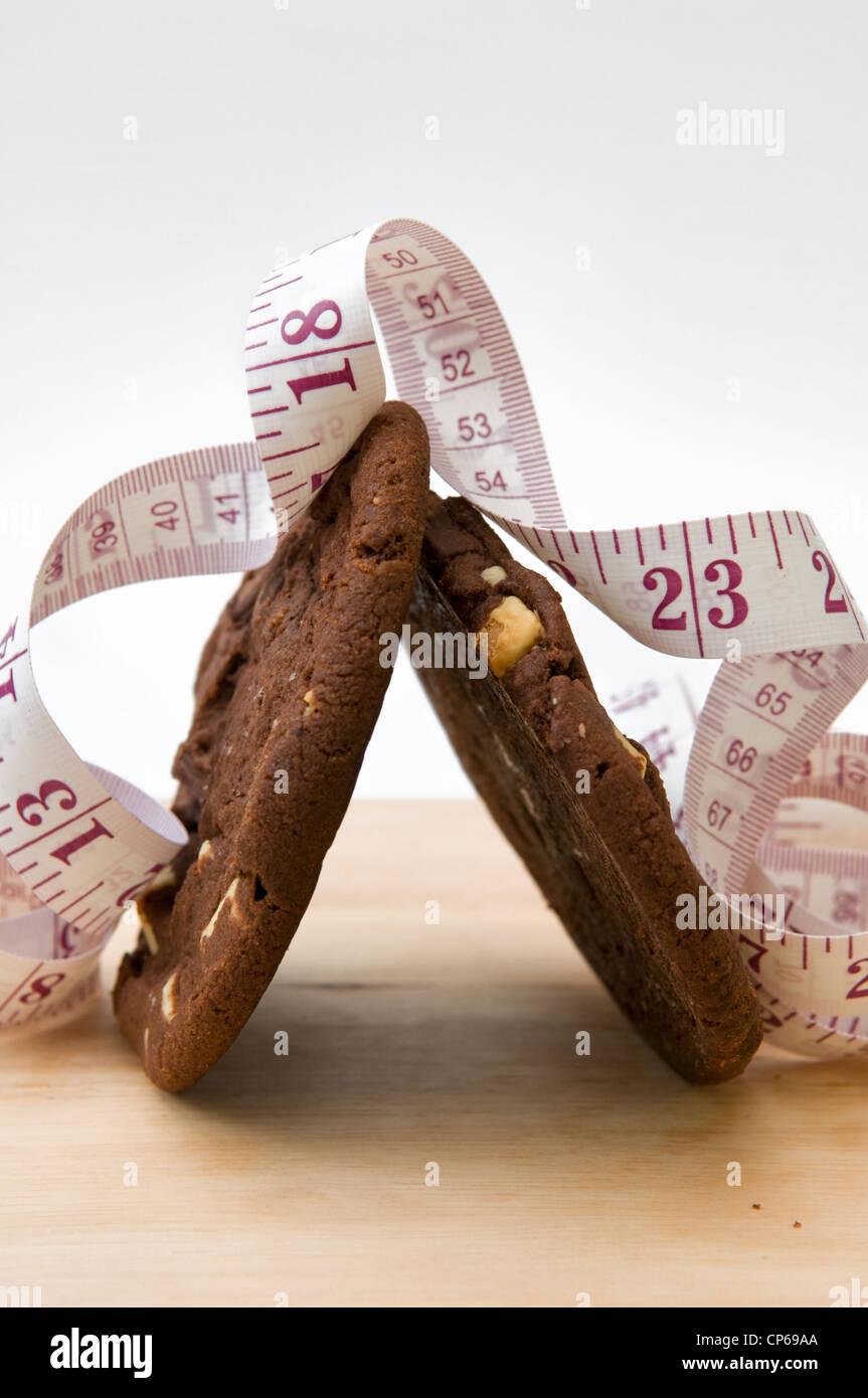Biscotti al cioccolato sul tagliere con nastro di misurazione raffiguranti concetto che mangiare i biscotti sarà Immagini Stock