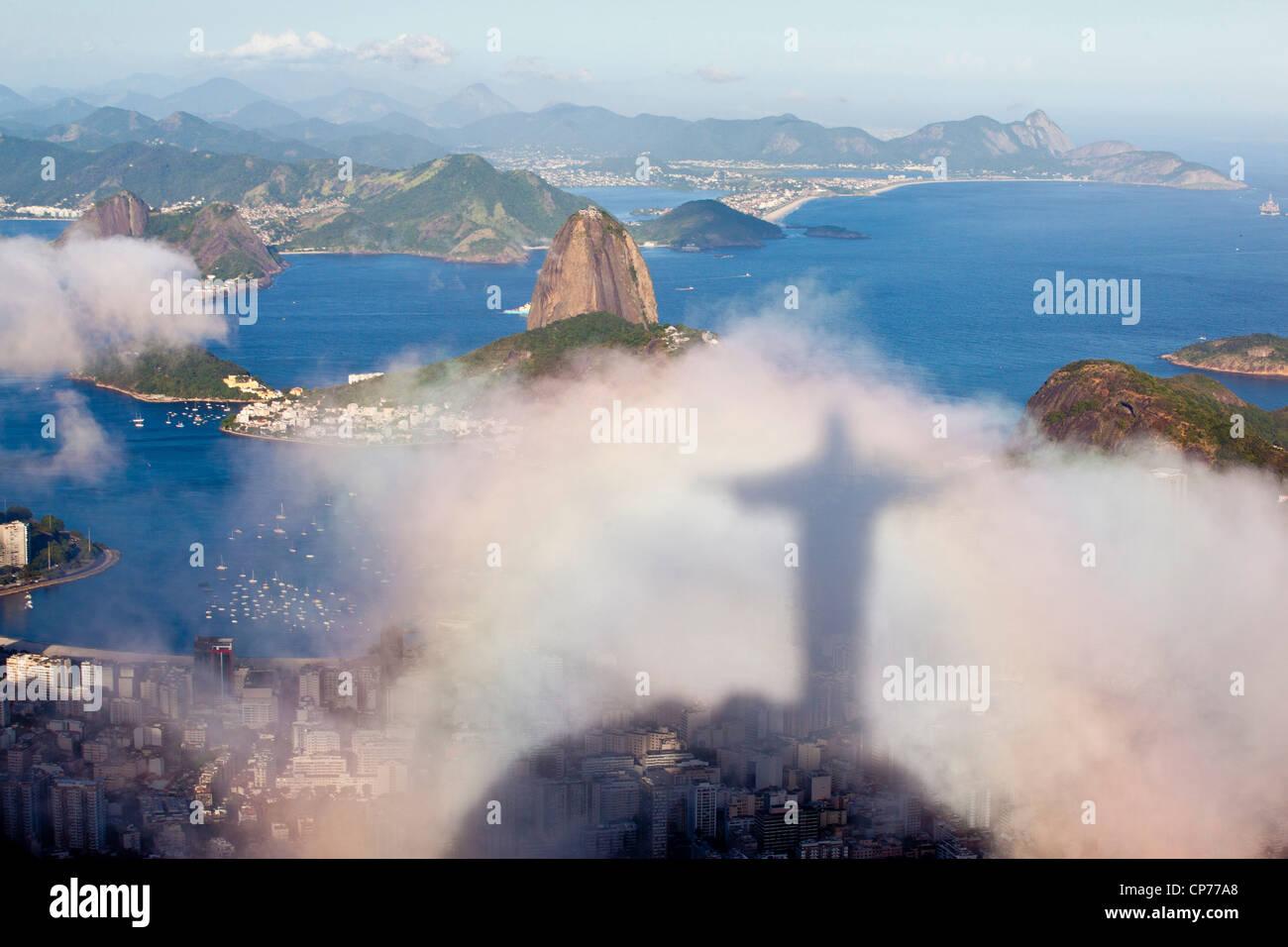 Ombra della statua del Cristo Redentor proiettata sul cloud, Sugar Loaf e Niteroi spiagge città sullo sfondo Immagini Stock