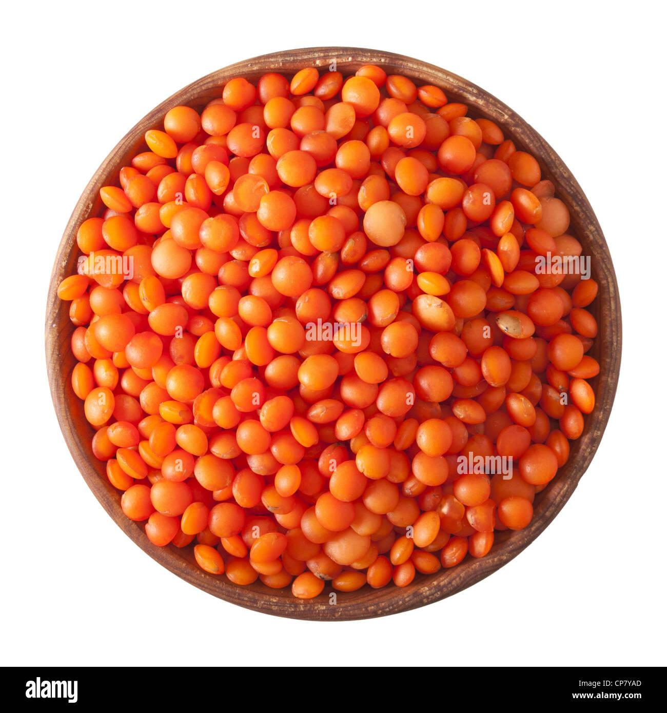 Ciotola di legno pieno di lenticchie rosse isolato su sfondo bianco Immagini Stock