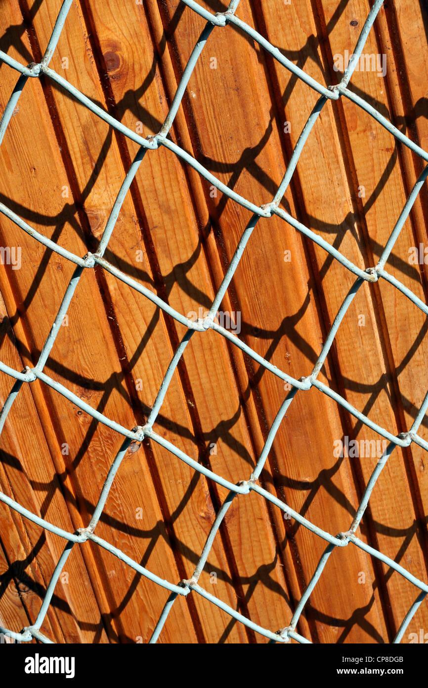 Texture di sfondo le tavole di pino e traliccio metallico con la luce del sole. Immagini Stock