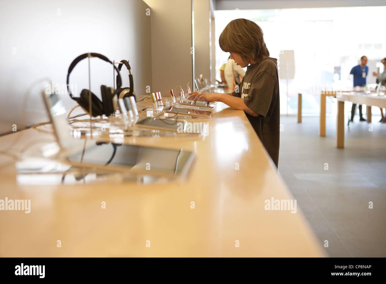 Bambino di nove anni tenta di eseguire la versione più recente del tablet ipad presso un negozio Apple Store. Immagini Stock
