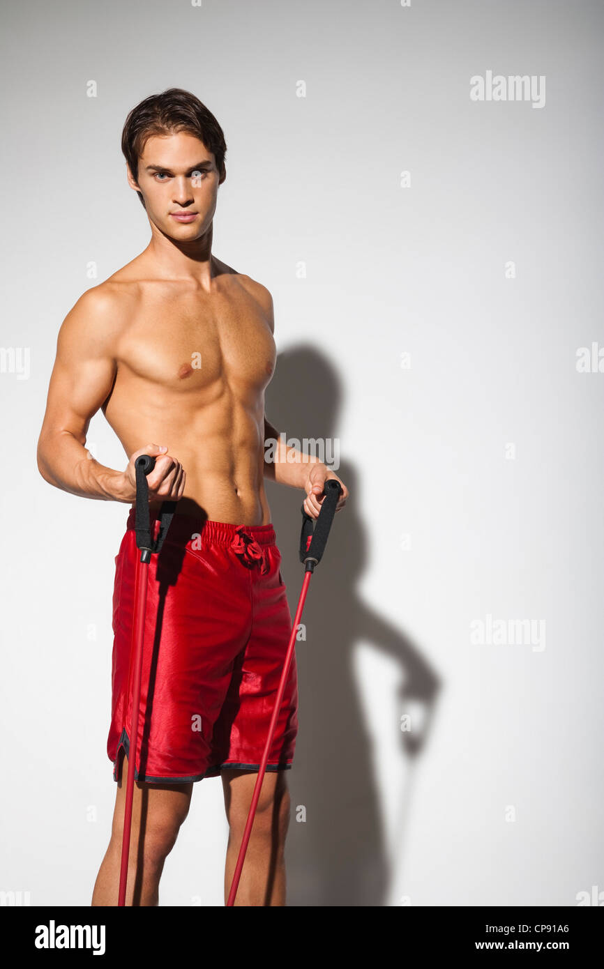 Ritratto di una sana e bella giovane uomo caucasico esercitando con bande di resistenza. Immagini Stock