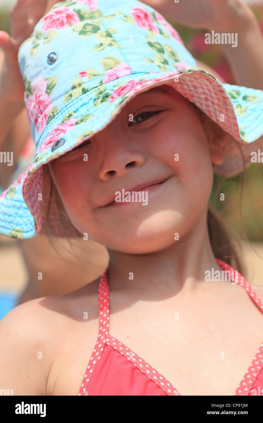 Felice bambina in un costume che indossa un floral cappello per il sole  presso la piscina d31abda48b46