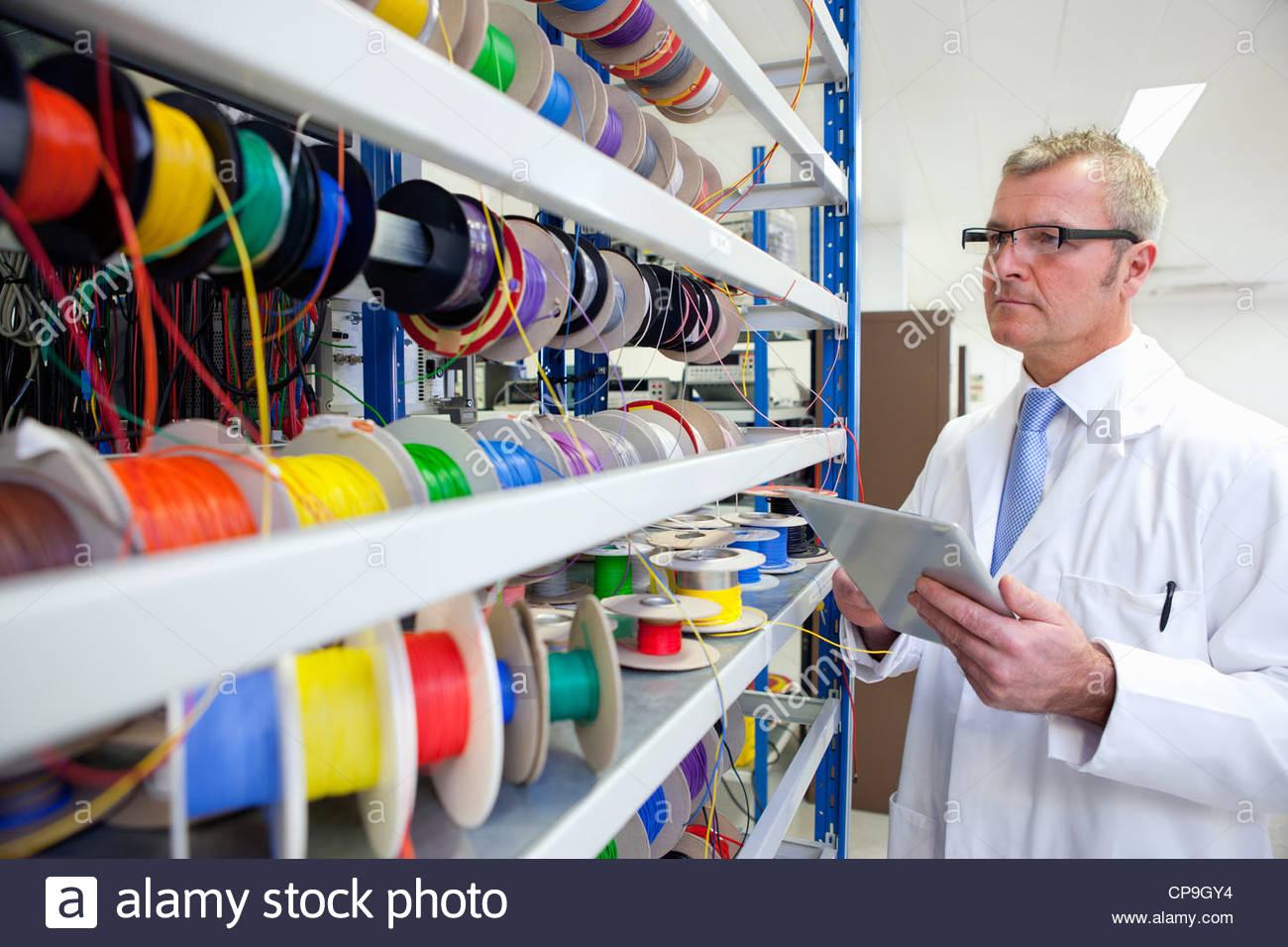 Ingegnere, inventario di vibranti di bobine di filo sulla tavoletta digitale in laboratorio Immagini Stock
