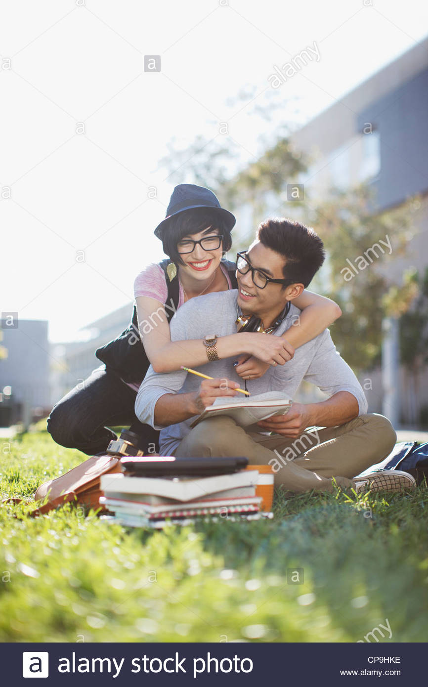 18-19 anni,20-24 anni,l'affetto,etnia asiatica,prenota,ragazzo,abbigliamento casual,caucasian,college,colore Immagini Stock