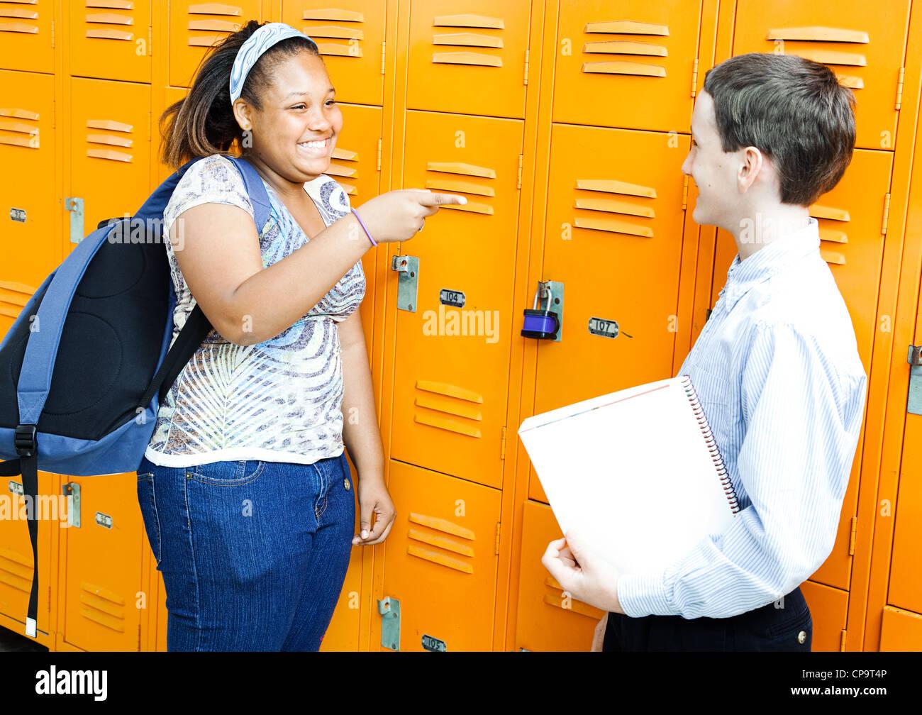 La scuola media di un ragazzo e una ragazza ridendo e scherzando insieme da loro armadietti. Immagini Stock