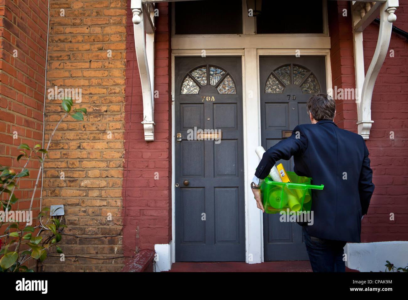 Uomo in piedi fuori casa con oggetti di lavoro Immagini Stock
