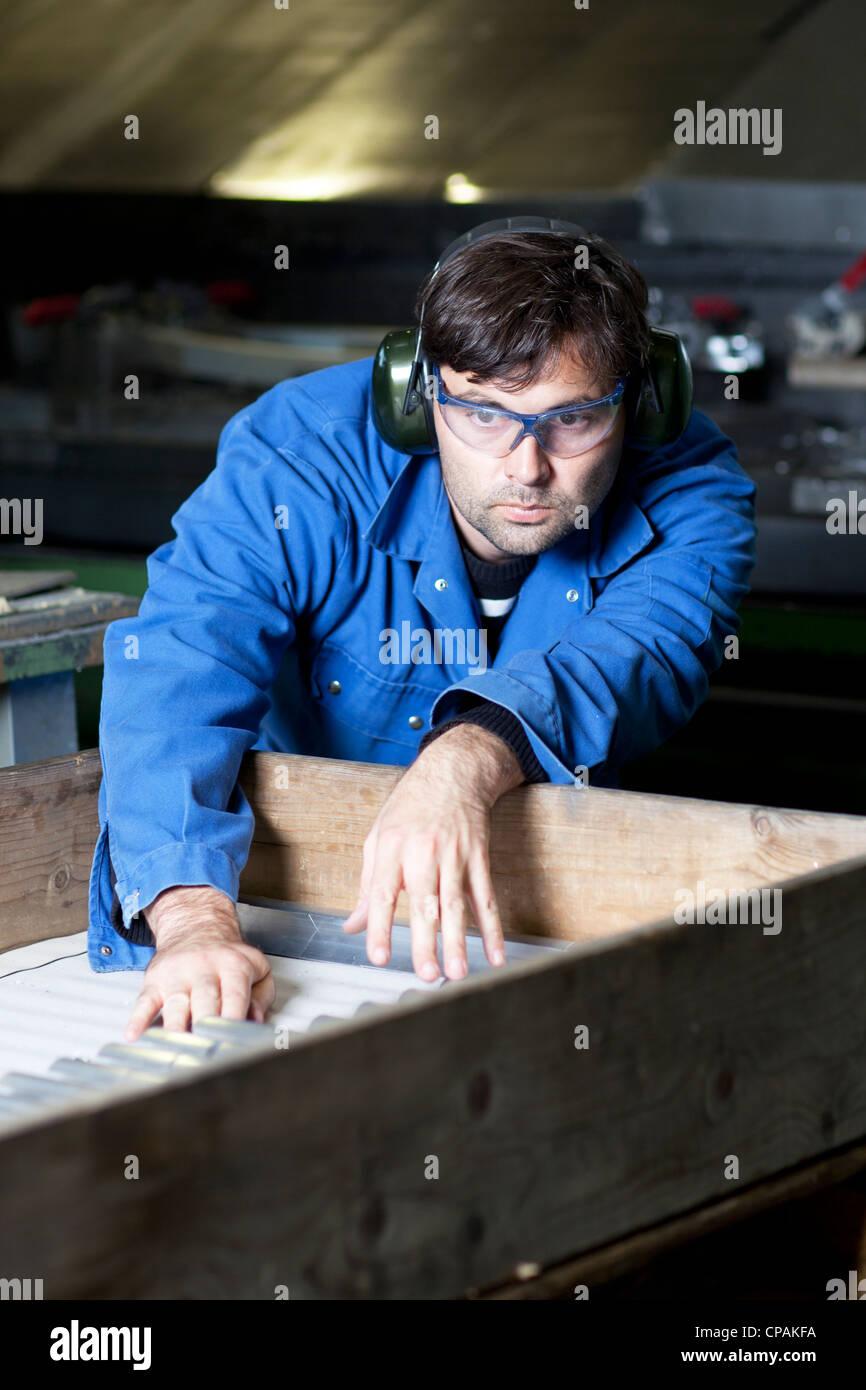Collare blu lavoratore a macchina in fabbrica Immagini Stock