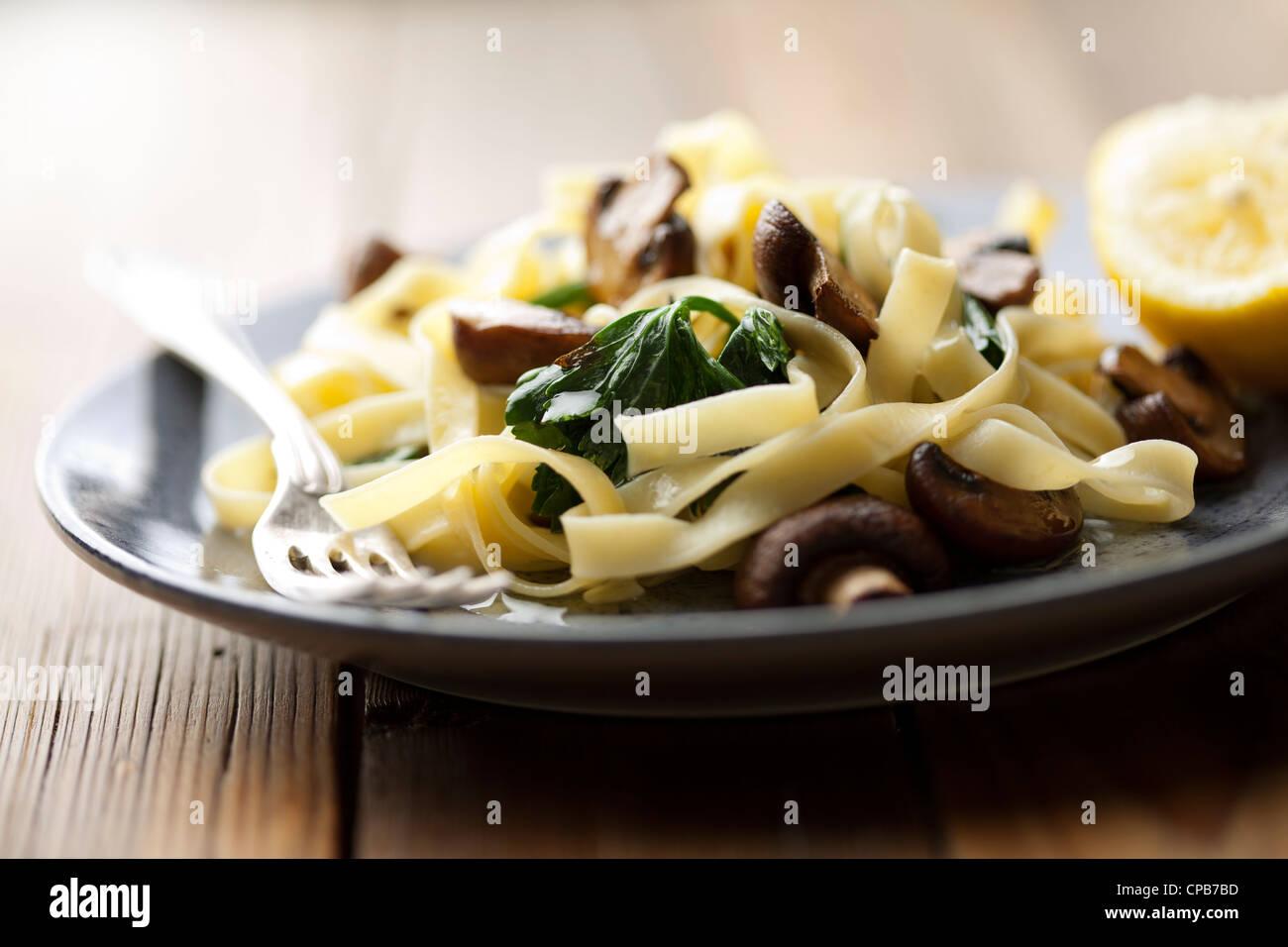 Piatto vegetariano con tagliatelles, spinaci e funghi Immagini Stock