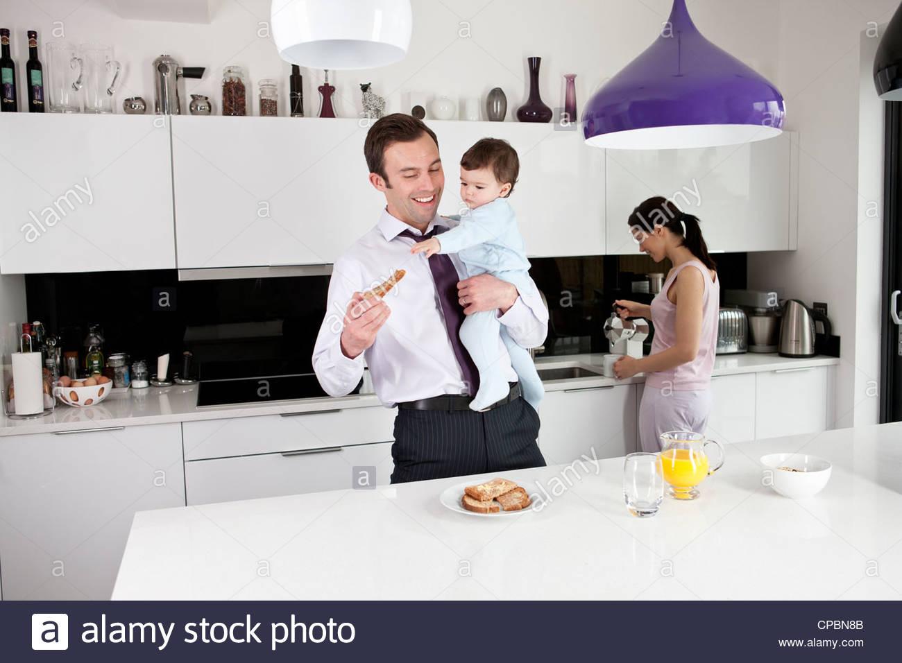 Un padre cercando di mangiare la sua prima colazione mentre tiene il suo Figlio bambino Immagini Stock