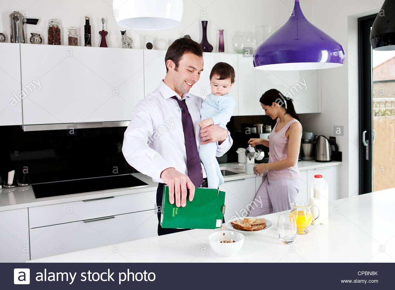Un padre tiene il suo Figlio bambino mentre facendo colazione Immagini Stock