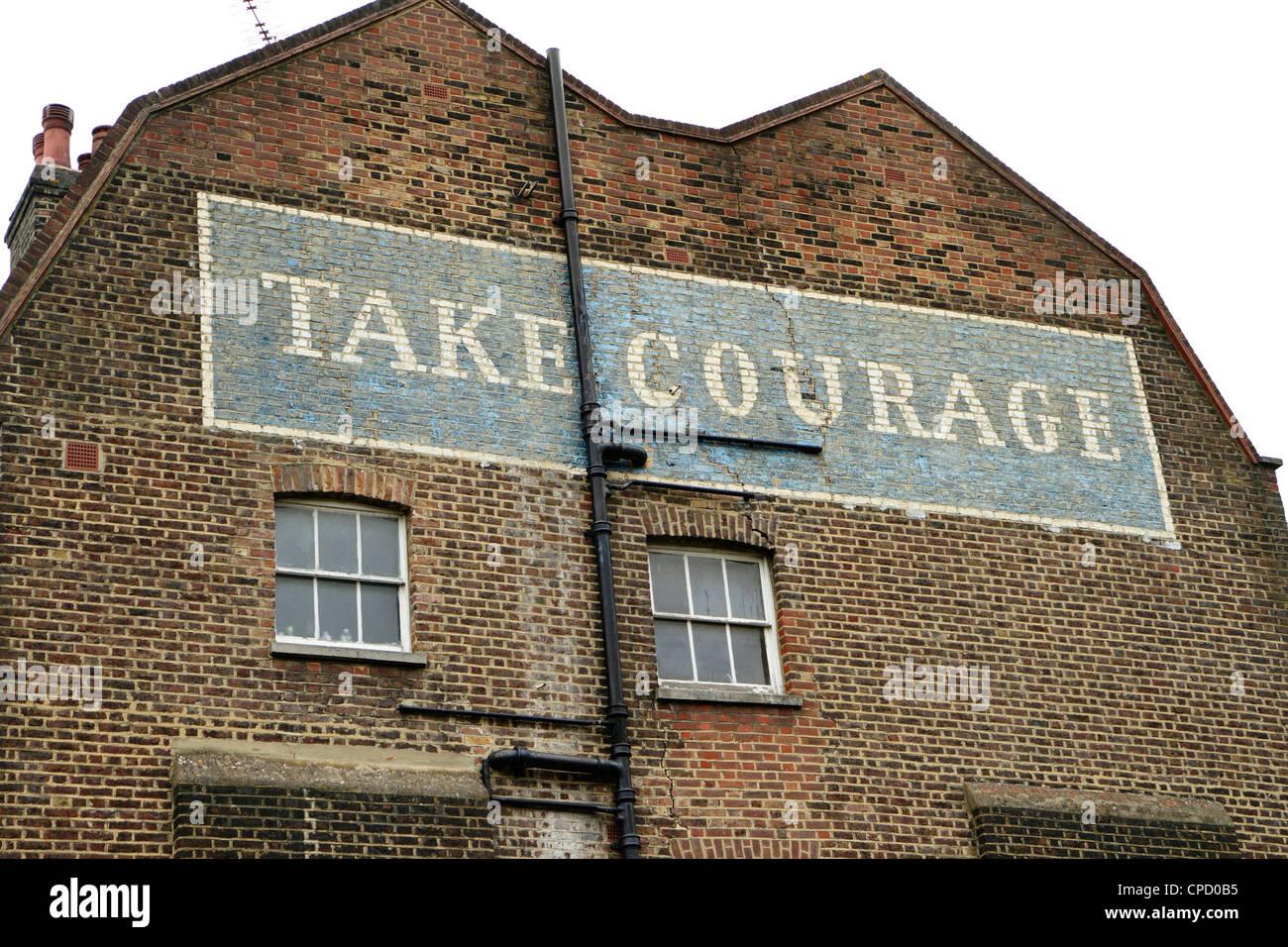 Dipinto 'prendere coraggio' birra pubblicità sul lato dell'edificio, London, Regno Unito Immagini Stock